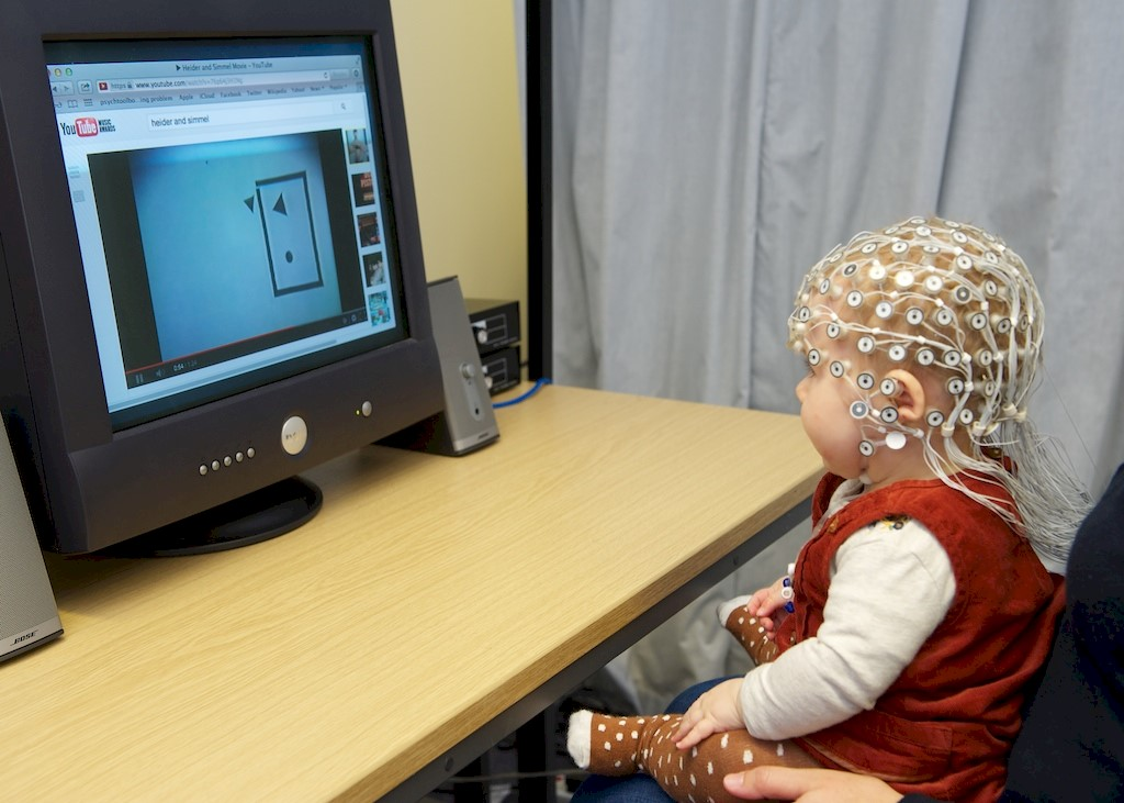 Baby wearing electrode cap taking part in an EEG experiment